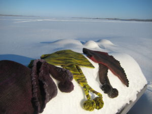 Three triangel scarfs on a snowy stone. Colours winered, yellow-green and autumn. Back lake Inari.